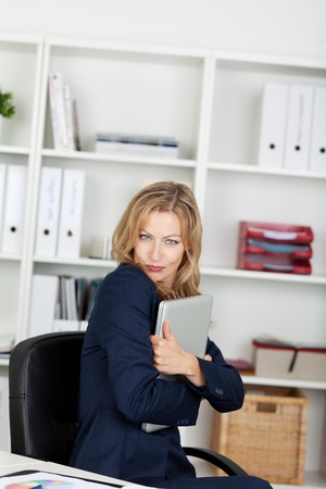 Portrait of happy mid adult businesswoman embracing laptop in office Stock Photo - 21261082