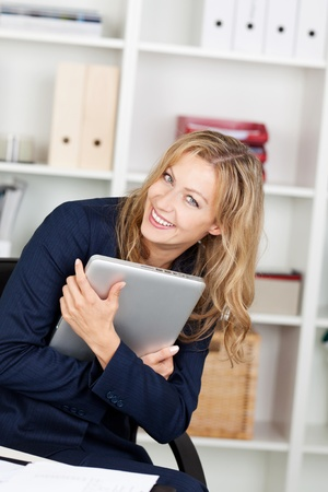 Portrait of smiling mid adult businesswoman embracing laptop in office photo