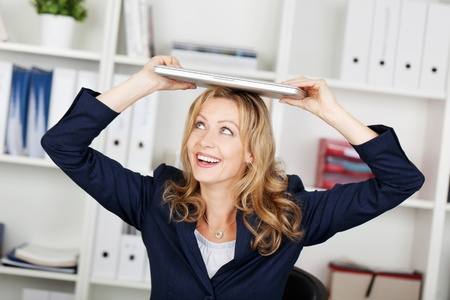 Smiling businesswoman with laptop on her head photo