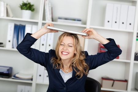 clenching teeth: Playful businesswoman with laptop on head clenching teeth in office
