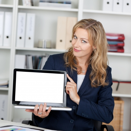 Mid adult businesswoman displaying laptop with blank screen photo