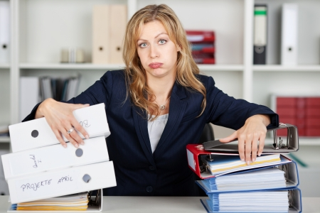 Portrait of bored mid adult businesswoman behind stacked binders at office desk photo