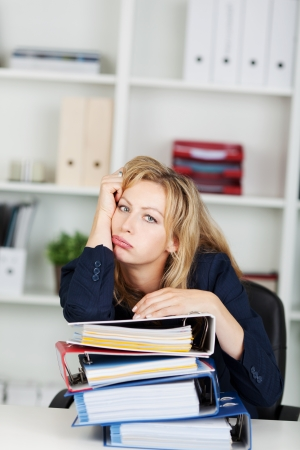 Portrait of bored mid adult businesswoman leaning on stacked binders at office desk photo