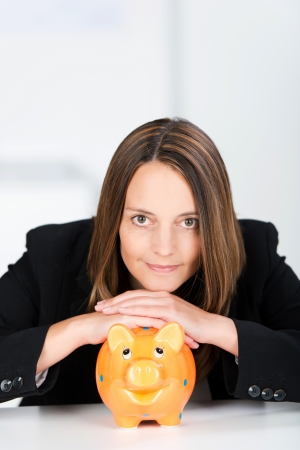 coinbank: Portrait of serious businesswoman with piggy bank at desk