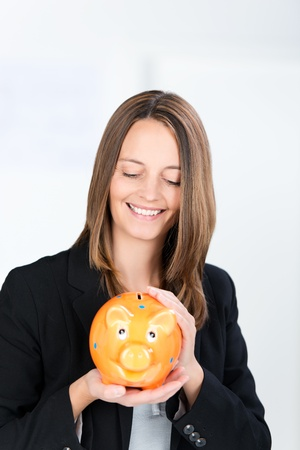 coinbank: Portrait of happy businesswoman holding piggy bank in office