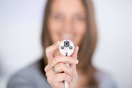 Closeup of smiling mid adult woman with electric plug at home photo