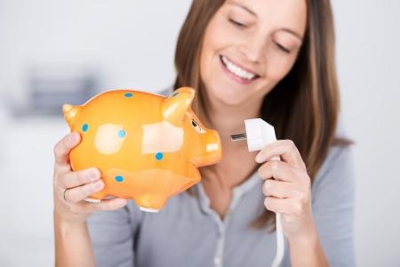 Retrato de divertida mujer de mediana edad sosteniendo un enchufe eléctrico y una hucha