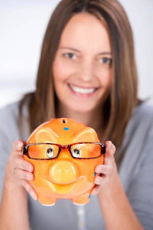 coinbank: Portrait of happy businesswoman holding piggy bank with glasses in office Stock Photo