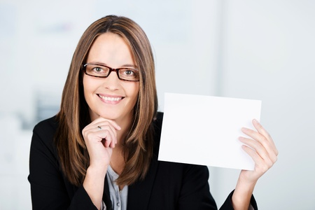 Mid adult smiling businesswoman holding white paper in office - copy space for you text photo