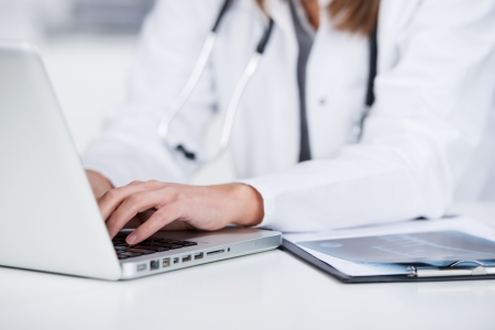 Midsection of female doctor using laptop at desk photo