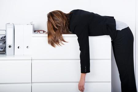 Zijaanzicht van zakenvrouw slapen op de balie in het kantoor Stockfoto