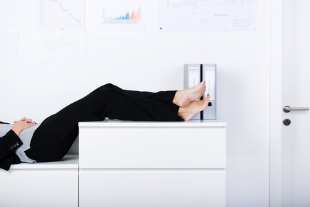 Side view of businesswoman legs sleeping on counter in office photo