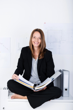 Full length portrait of mid adult businesswoman with binder sitting on counter at office photo