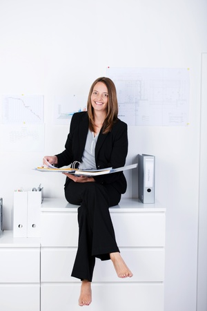 Full length portrait of happy mid adult businesswoman with binder sitting on counter at office