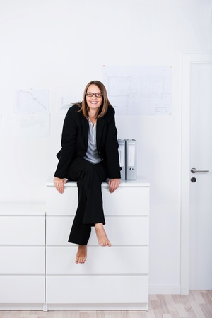 Full length portrait of happy businesswoman sitting on counter at office photo