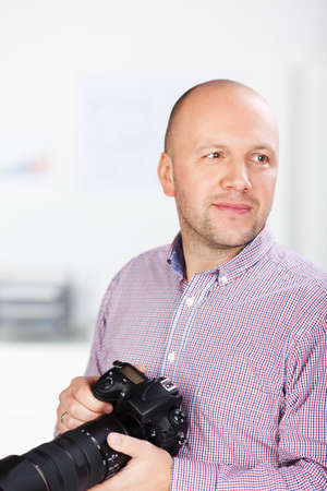 looking away from camera: Mature businessman holding SLR camera while looking away in office