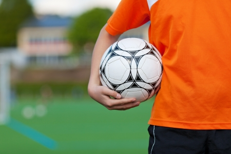 soccer ball on grass: young boy holding soccer ball on soccer field Stock Photo