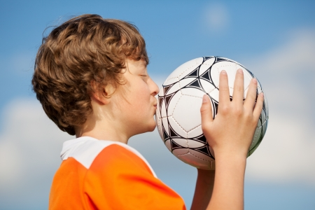 closed club: Side view of young boy kissing soccer ball against sky