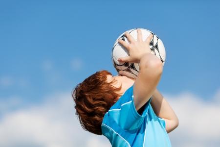 boys soccer: happy winner kissing soccer ball against blue sky