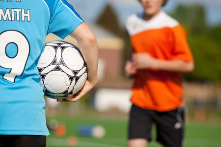 Midsection of boy holding soccer ball with friend running in background photo