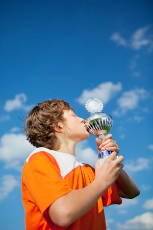 Low angle view of little boy kissing trophy against sky photo