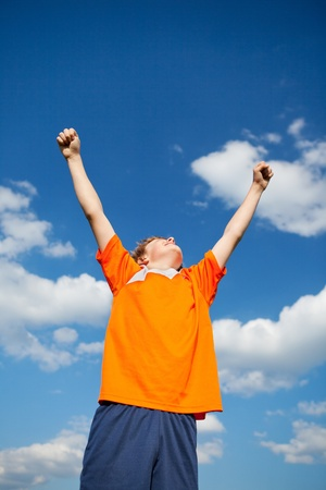 victory stand: Low angle view of little boy with arms raised celebrating victory against sky Stock Photo