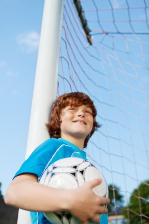 cool kids: Low angle view of little boy holding soccer ball while leaning on net pole