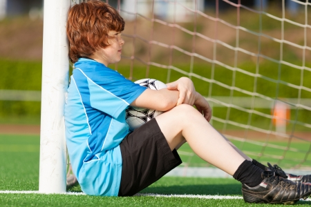 sad looking boy leaning at goal on soccer field photo