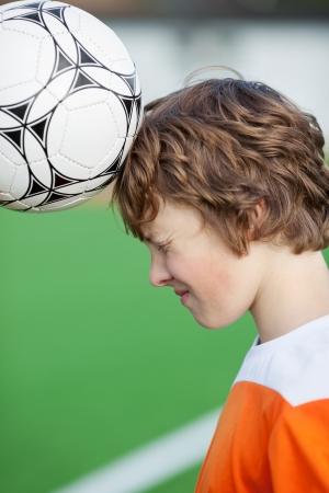 10 代の少年 headering サッカーのフィールドでボール