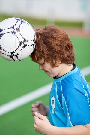 Side view of little soccer player headering the ball in field photo
