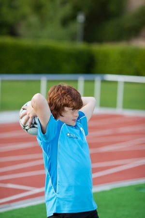 concentrating: Young boy throwing ball on field Stock Photo