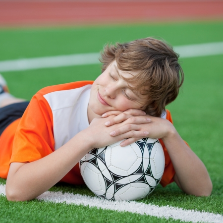 teenager lying with ball on soccer field photo