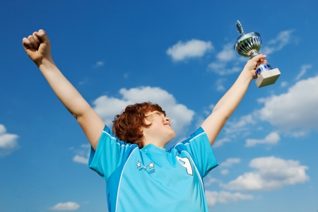 portrait of a champion celebrating victory against blue sky Stock Photo
