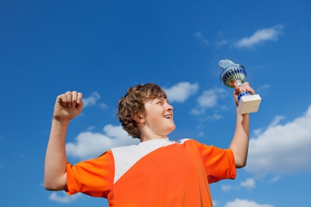 low prizes: Low angle view of little boy celebrating victory while holding trophy against sky