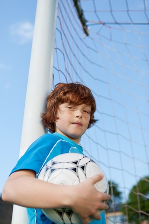 young soccer player leaning at soccer goal photo