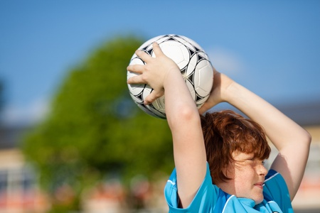 concentrating: side view of a young soccer player throwing in