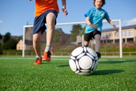 Little boys playing football on field photo