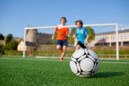 cancha deportiva futbol: ángulo de visión baja de dos jugadores de fútbol jóvenes corriendo hacia el balón de fútbol