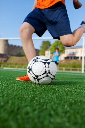 low angle view of a boy kicking soccer ball on field photo