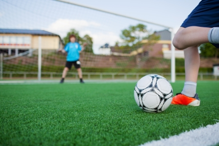 Low section of boy kicking soccer ball with goalkeeper in background photo