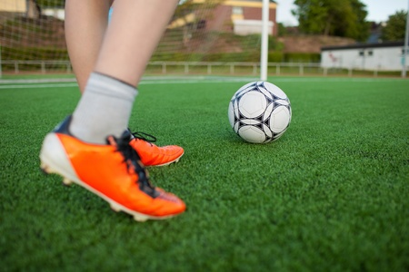 football shoes: Low section of little boy playing soccer on field