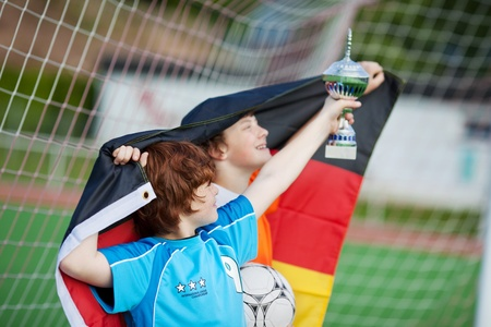 football european championship: young soccer players with trophy and german flag