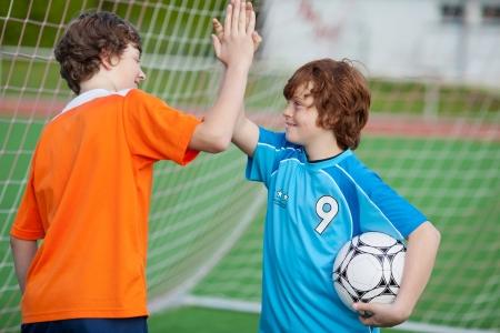フィールドでハイファイブを与える幸せのフットボール選手