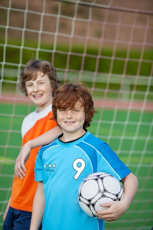 two young players standing in front of soccer goal photo