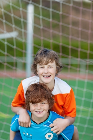 adversaries: two happy friends having fun on soccer field