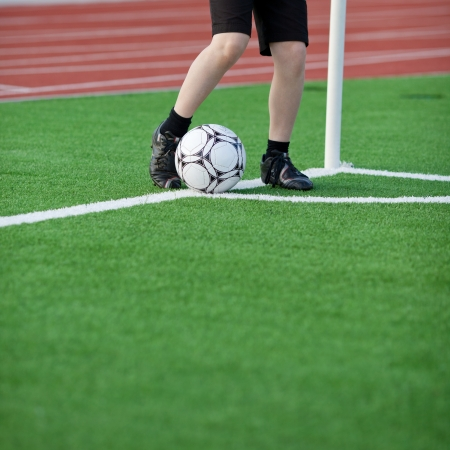 Low section of boy kicking soccer ball at corner on field Stock Photo