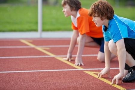 ni�o corriendo: Vista lateral de corredores masculinos en posici�n de salida en pista de carreras