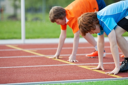 running on track: Side view of two young male runners on starting position at racetrack Stock Photo