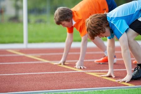 ropa deportiva: Vista lateral de dos corredores varones j�venes en la posici�n de partida en el circuito