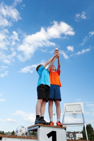 Low angle view of boys holding trophy while standing on winners podium against sky photo
